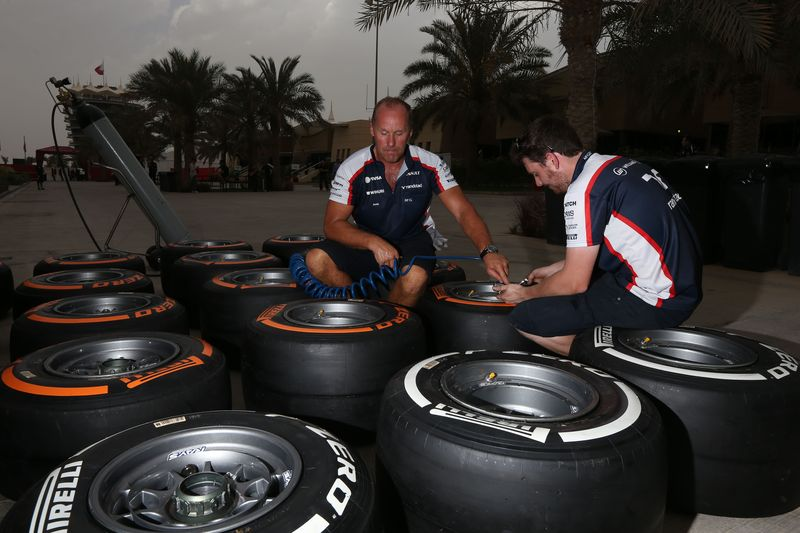 Mechanics working on tyres in the paddock
